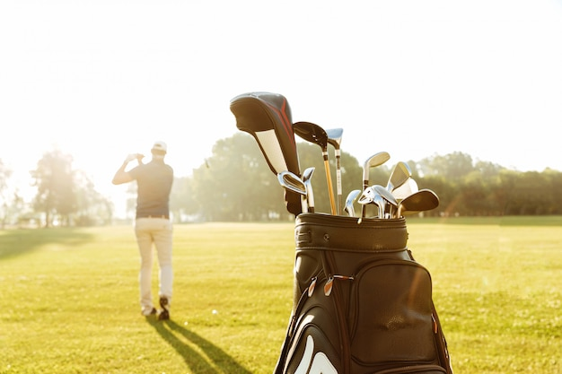 Back view of a male golfer swinging golf club Free Photo