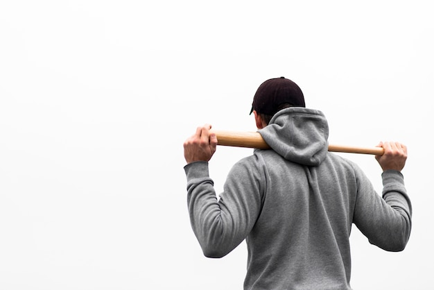 Back view of man holding baseball bat on shoulders Free Photo