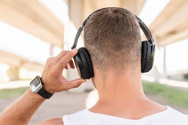Back view man listening to music through headphones Free Photo