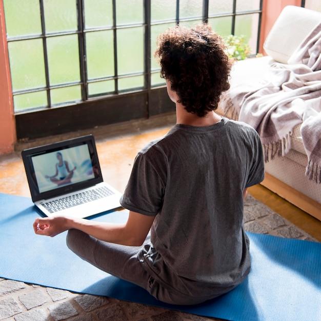 Вид сзади человек медитирует дома Premium Фотографии