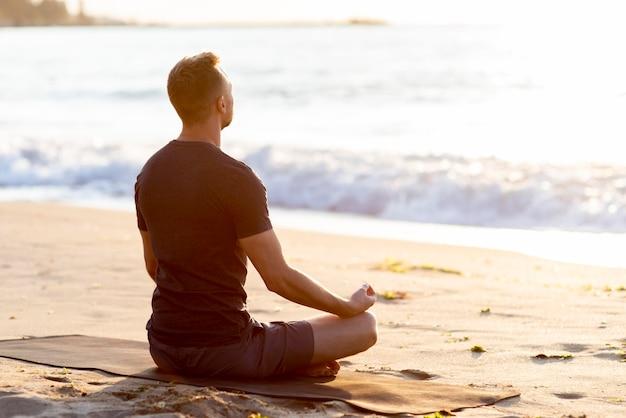 Вид сзади человек расслабляющий на пляже за пределами Бесплатные Фотографии