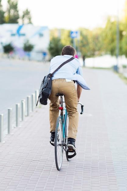 Вид сзади человек, езда на велосипеде на открытом воздухе Бесплатные Фотографии