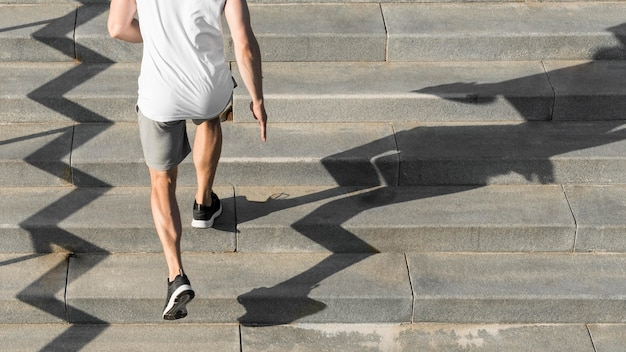 Back view man running on stairs with copy space Premium Photo