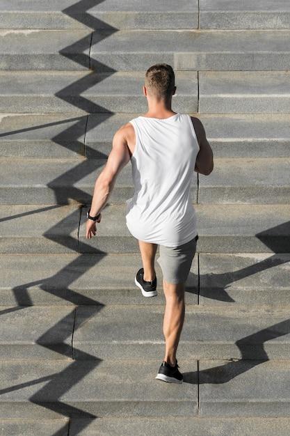 Vista posteriore uomo che corre sulle scale Foto Gratuite