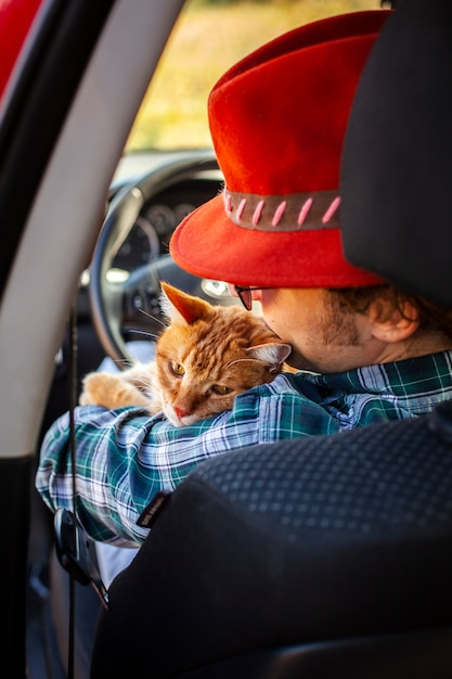 Back view man sitting in driving seat with a cat Free Photo