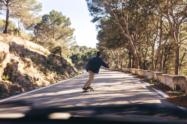 Back view of man with skateboard on road Free Photo