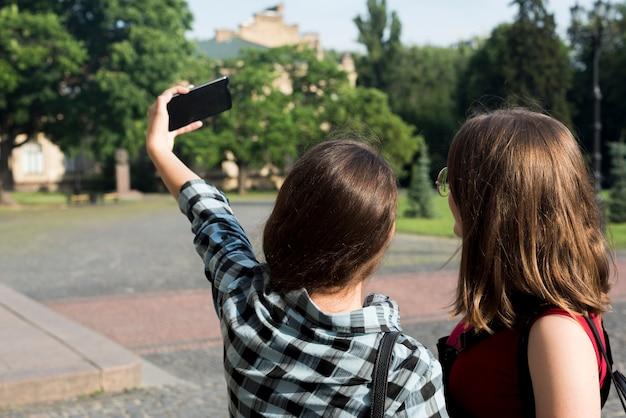 Back view medium shot of teenage girls taking a selfie Free Photo