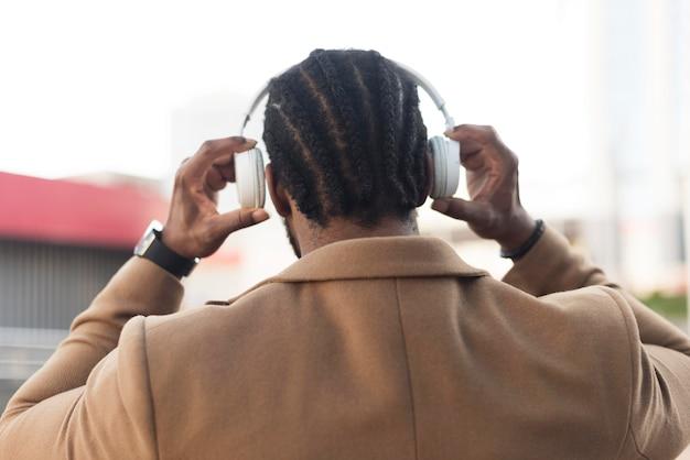 ヘッドフォンを介して音楽を聞いて背面図現代人 無料写真