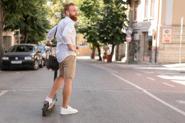 Vista posteriore uomo moderno su scooter Foto Gratuite