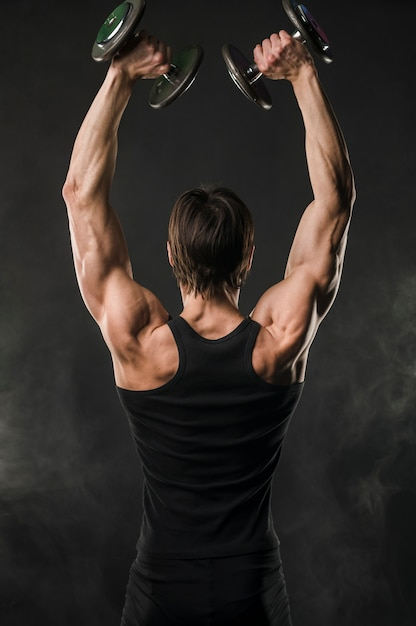 Back view of muscled man lifting up weights Free Photo