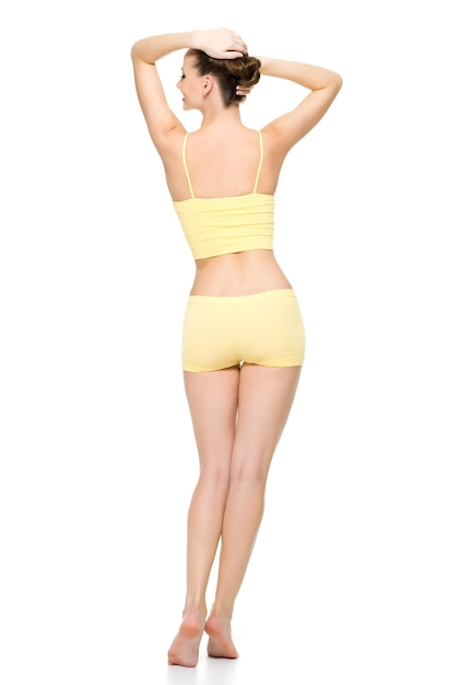 白い壁に分離されたポーズの黄色い下着で美しいスポーティな女性の身体の背面図 無料写真