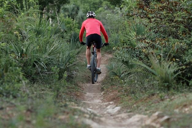 熱帯林の狭い歩道に乗って、自転車用ヘルメットと赤いサイクリングジャージを身に着けているサイクリストの背面図。 Premium写真