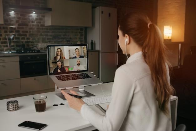 自宅のデスクトップコンピューターでのビデオ会議で、ビジネスについて同僚とリモートで話している女性従業員の背面図。オンライン会議の多民族のビジネスチーム。 Premium写真