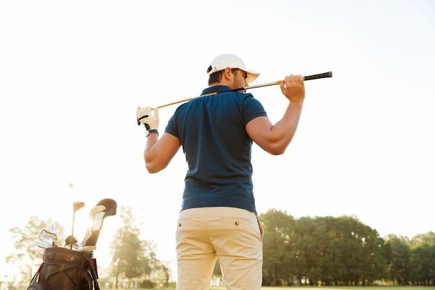 Вид сзади мужского игрока в гольф на поле с клубным мешком Бесплатные Фотографии