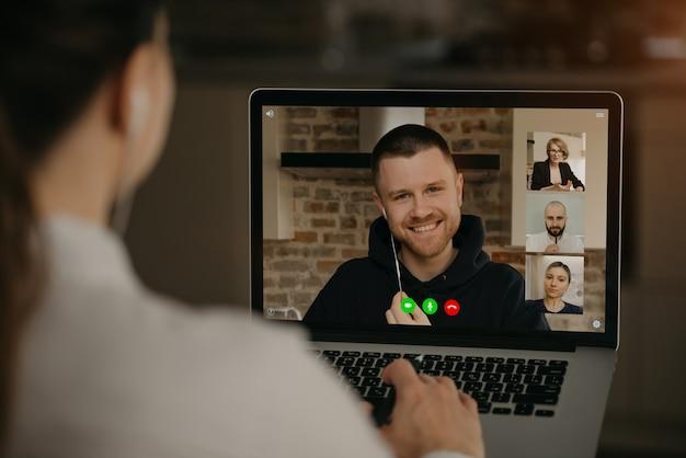 ノートパソコンでビデオ通話でビジネスパートナーや同僚と話している女性の背面図。男は、ウェブカメラ会議で同僚と話します。オンライン会議を持つ多民族のビジネスチーム Premium写真