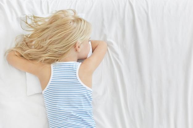 何かを夢見て、ストライプのtシャツを着て、健康的な睡眠をとり、白い枕の上に胃の上に横たわって、愛らしいブロンドの女の子の背面図。放課後ベッドで寝ているのんきな屈託のない小さな子供 無料写真