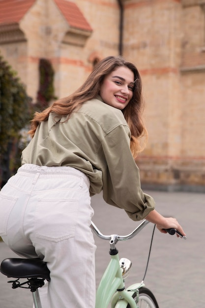 야외에서 그녀의 자전거를 타고 아름 다운 웃는 여자의 뒷면 무료 사진