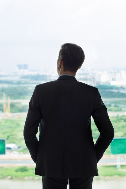 back view of businessman looking at city in window photo free download