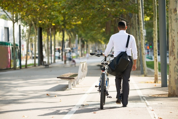 Back View of Businessman Walking with Bike in Park Free Photo