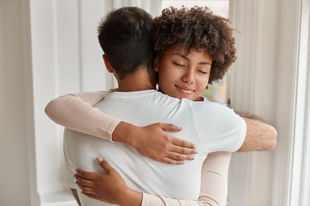白人男性の背面図は彼女のガールフレンドを抱きしめ、お互いに密接に立ち、愛とサポート、慰め、共感を表現し、良好な関係を持っています。人、ケア、人間関係の概念 無料写真