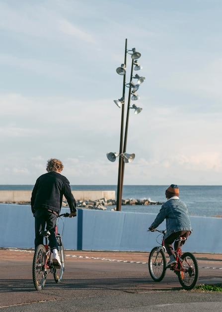 自転車で屋外の子供友達の背面図 無料写真
