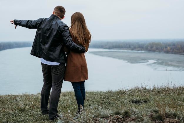 Вид сзади пары, любуясь видом на озеро с копией пространства Бесплатные Фотографии