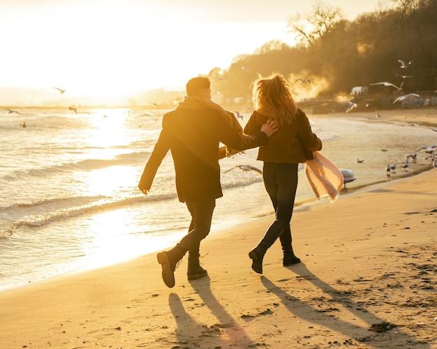 Вид сзади пары, идущей на пляже зимой Бесплатные Фотографии