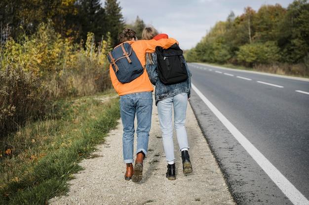 Вид сзади пары, идущей вместе на обочине дороги Бесплатные Фотографии