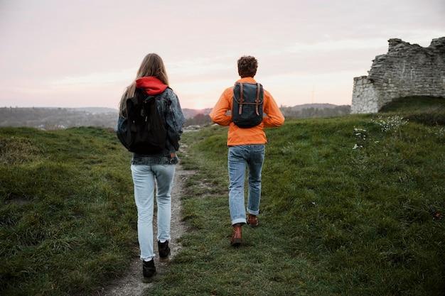 一緒にロードトリップ中に歩いているカップルの背面図 Premium写真