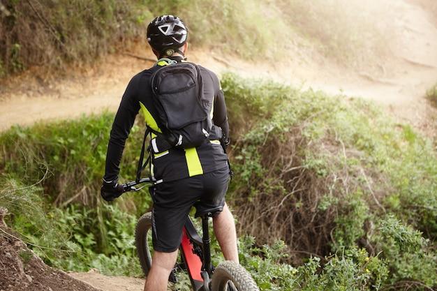 田舎の丘陵地帯で電気自転車に乗って黒い服を着たサイクリストの背面図 無料写真