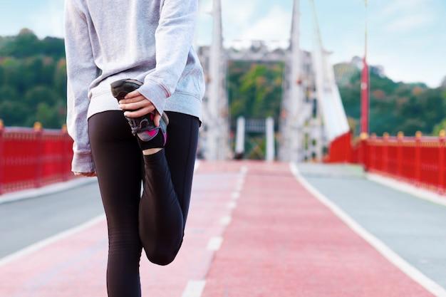 灰色のスニーカーの女性の足の背面図は、マラソンを実行する前に、朝のストレッチを行っています。運動の若い女性がジョギングの準備をしています。スポーティで健康的なライフスタイルのコンセプトです。 Premium写真
