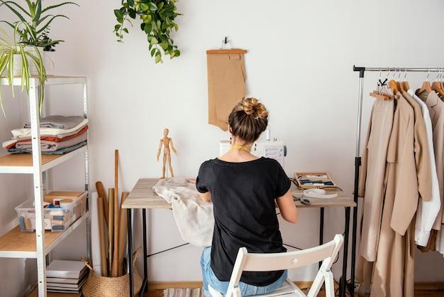 スタジオで働く女性の仕立て屋の背面図 無料写真