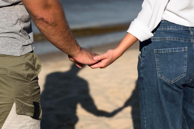 Вид сзади влюбленных, взявшись за руки на пляже Бесплатные Фотографии