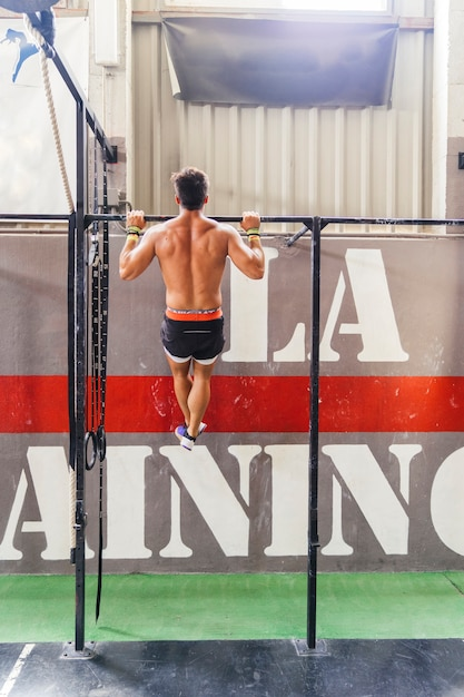 Back view of man doing pull ups Free Photo