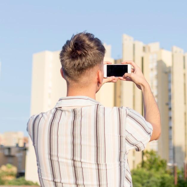 Вид сзади человека, фотографирующего на открытом воздухе с помощью смартфона Бесплатные Фотографии