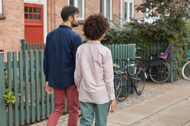 混血カップルの背面図は手をつないで、屋外散歩の後に家に帰る、自転車に乗る、スタイリッシュな服を着る 無料写真