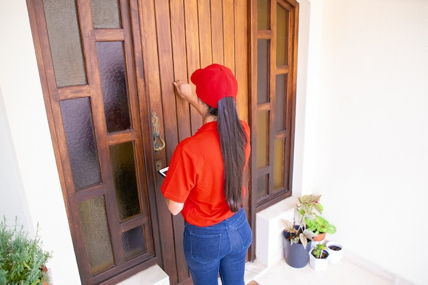 ドアをノックしてタブレットを持っているpostwomanの背面図。ドアの前に立って顧客に注文を届ける赤い制服を着たブルネットの女性宅配便。配送サービスとポストコンセプト 無料写真