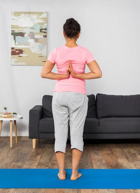 Вид сзади беременной женщины, тренирующейся дома Бесплатные Фотографии