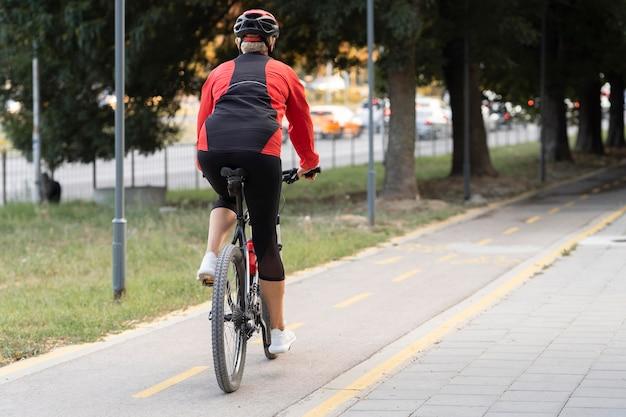 Вид сзади пожилой женщины, езда на велосипеде на открытом воздухе с копией пространства Бесплатные Фотографии