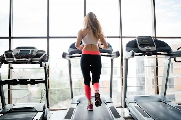 スポーツウーマンがジムでトレッドミルでトレーニングの背面図。フィットネス女性。 無料写真