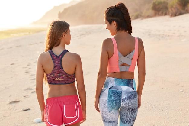 スポーティな女性の背面図は一緒にスポーツに行き、海岸を歩いて、トップスとショートパンツまたはレギンスを着ています 無料写真