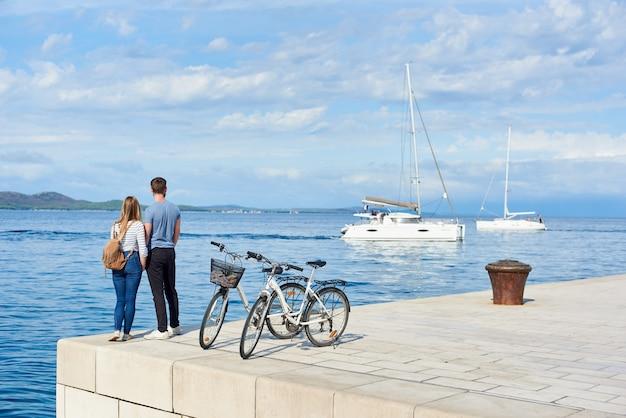 自転車に立っているバックパックを持つ観光客カップル、男女の背面図 Premium写真