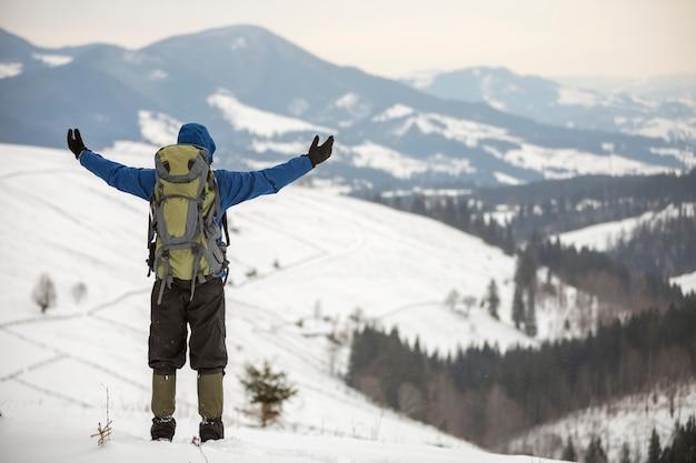 Вид сзади туриста в теплой одежде с рюкзаком, стоящим с поднятыми руками на горной поляне на фоне пространства для копирования древесного горного хребта и облачного неба. Premium Фотографии