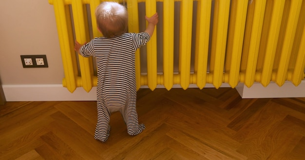 Вид сзади неузнаваемого малыша в полосатых гусеницах касаясь желтой теплой батареи возле стены дома Premium Фотографии