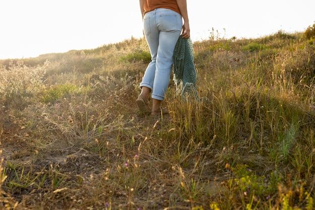 Вид сзади женщины в траве на открытом воздухе Бесплатные Фотографии
