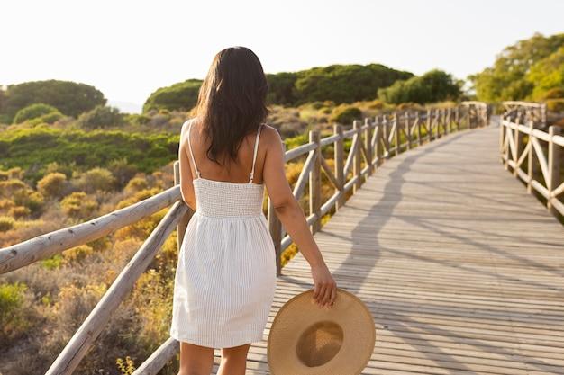 Вид сзади женщины в природе с шляпой Бесплатные Фотографии