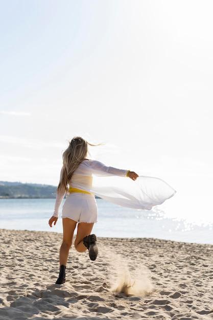 ビーチの砂の上を走っている女性の背面図 無料写真