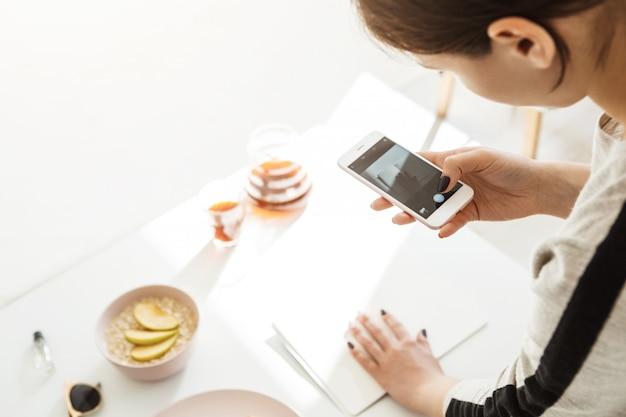 Вернуться мнение женщины, принимая современные фотографии на телефоне. Бесплатные Фотографии