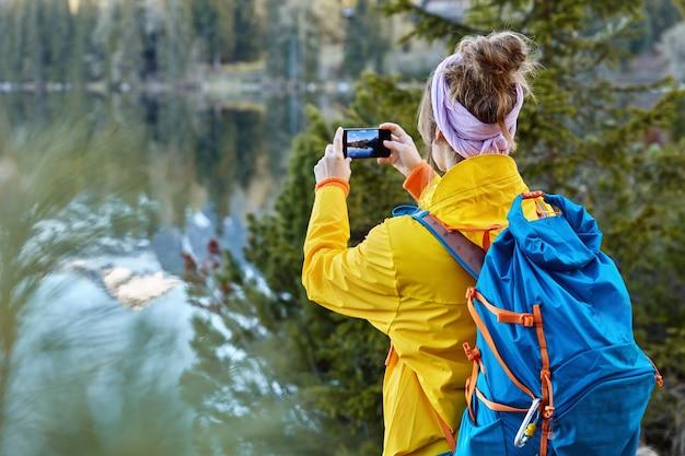 여성 여행자의 뒷모습이 현대 휴대 전화 카메라로 사진을 찍고 산 호수 근처의 경치를 포착하고 도로 여행을합니다. 무료 사진