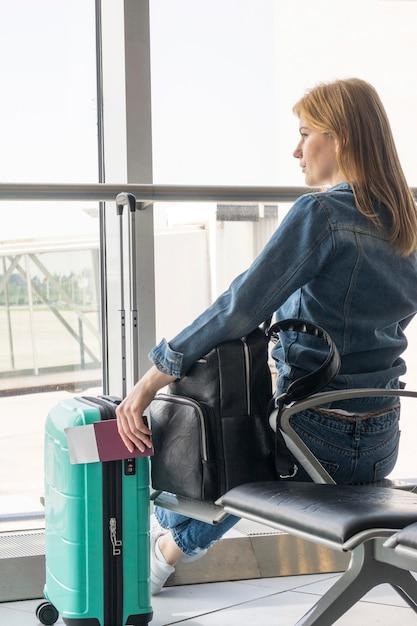Вид сзади женщина ждет в аэропорту Бесплатные Фотографии